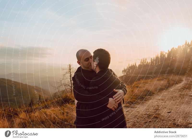Men hugging and kissing in forest Homosexual Couple Park Kissing Love holding hands Forest Lanes & trails Beautiful weather Closed eyes Sun Nature Man romantic