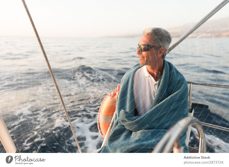 Smiling man in towel on yacht on water Man Yacht Water Adults Ocean Floating Towel Beautiful weather Watercraft Expensive Sunglasses Resting Positive Summer Sit