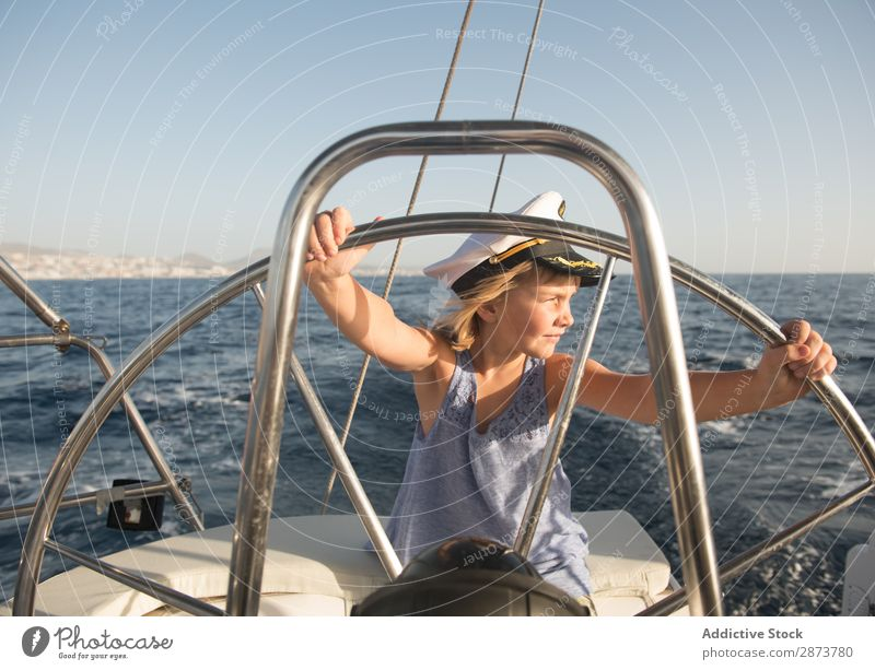 Smiling girl holding steering wheel on yacht on water Girl Yacht Water Steering wheel Captain Hat Ocean Child Floating Beautiful weather Watercraft Expensive