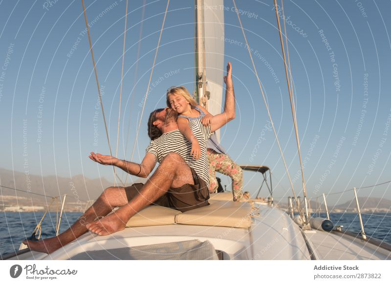 Man having fun with smiling girl and sitting on deck of yacht in sea Yacht Father Child Ocean Girl Floating Watercraft Daughter Deck Beautiful weather Kissing