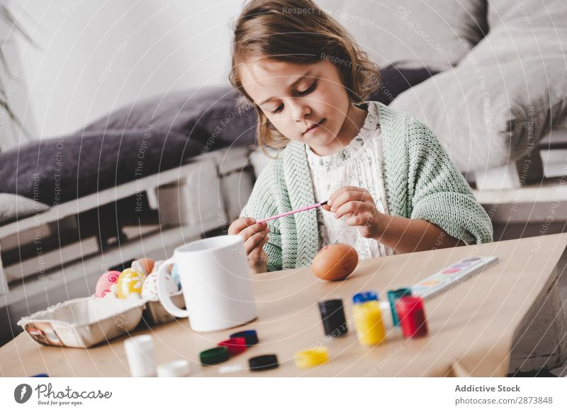 Girl coloring chicken egg at table Easter Egg Colouring Painting and drawing (object) Brush Child Table Spring Chicken Vacation & Travel Decoration
