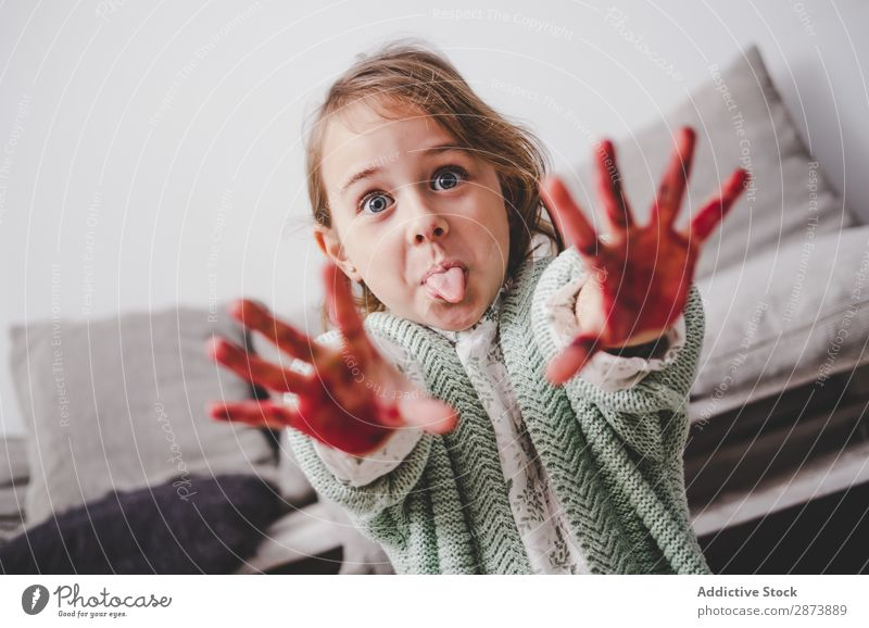 Girl with dirty hands showing tongue in room Hand Dirty Colour making face Tongue Room Sofa Indicate Painting (action, artwork) Funny Child Decoration