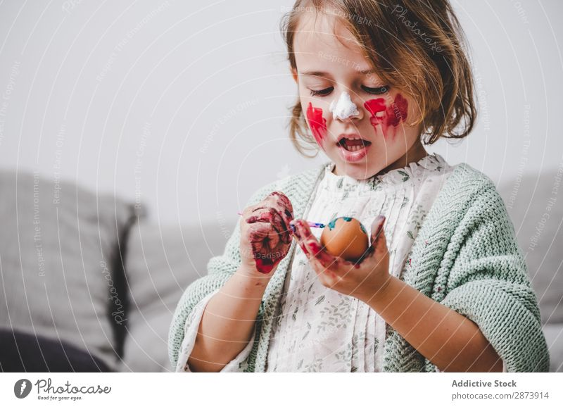 Girl with brush coloring chicken eggs at table in room Easter Egg Brush Room Sofa Colouring Funny Child Table Chicken Container Painting and drawing (object)