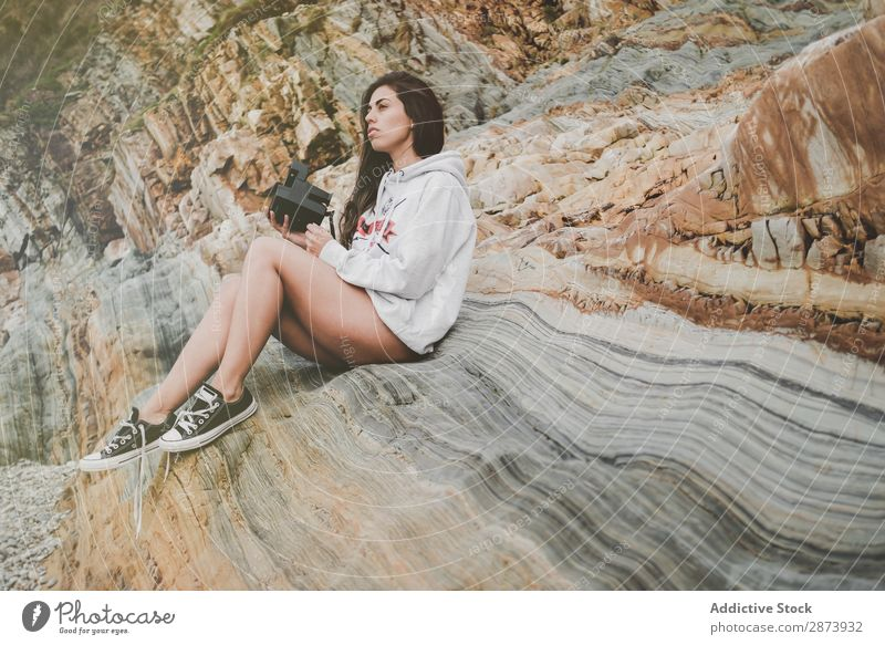 Lady with camera on shore near stones and water Woman Coast Ocean Camera Water Cheerful Retro Youth (Young adults) Lifestyle Stone Walking Underwear Sweater