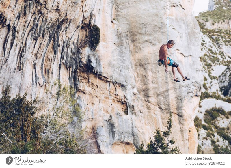 Anonymous climber handing on cliff Climber Cliff Hanging Rope Extreme Sky Blue Mountain Rock Sports challenge Action Success Power Height Adventure Risk belay