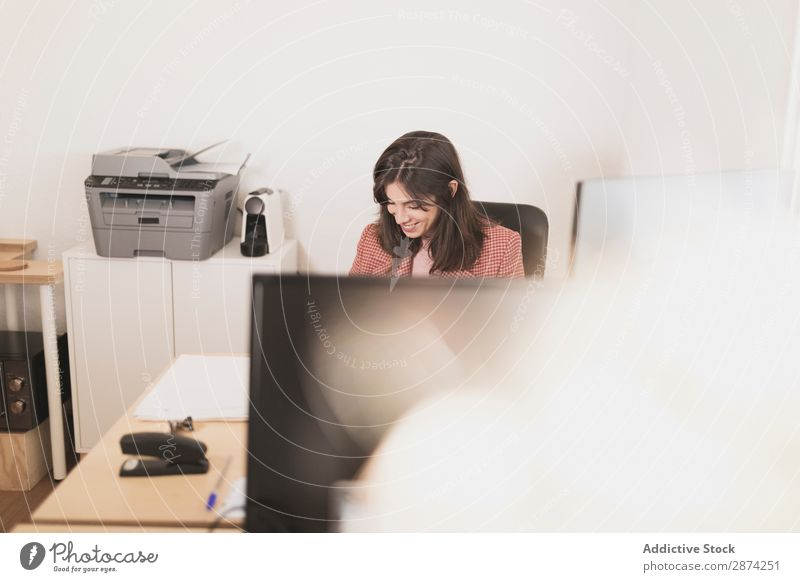Concentrated young lady using laptop and sitting at table Woman Workplace Earnest Screen Office Action Work and employment concentrated Cellphone Eyeglasses