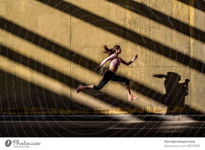 Young fit blonde woman jumping in the street Woman Jump Running Practice Fitness work out Lifestyle Movement Action Jogging Profile Horizontal Athletic Healthy