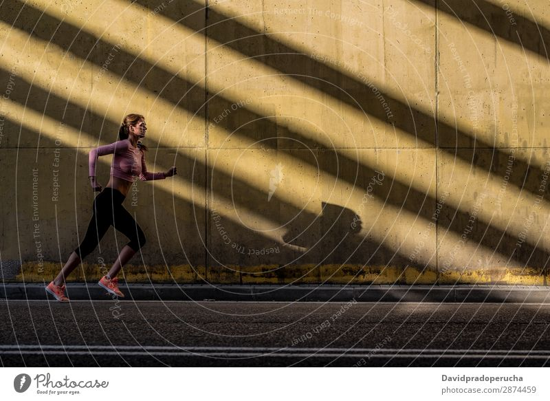 Young fit blonde woman running in the street Woman Running Practice Fitness Lifestyle Movement Action