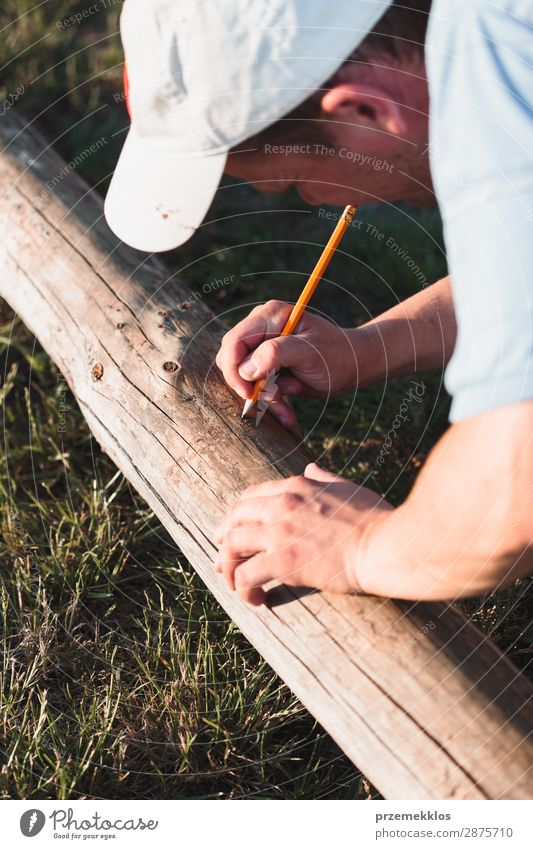 Man making mark while working in garden Summer Garden Work and employment Craft (trade) Tool Human being Adults Grass Building Hat Wood White Precision