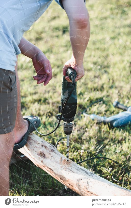 Man drilling hole in timber while working in garden Summer House (Residential Structure) Garden Work and employment Craft (trade) Tool Human being Adults Grass