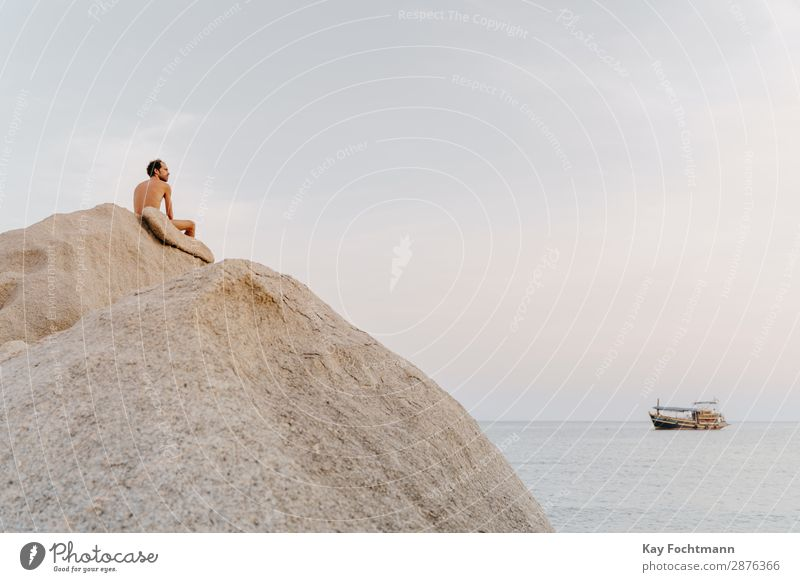 Man with free upper body sits on big rock by the sea Happy Healthy Fitness Wellness Life Harmonious Well-being Relaxation Calm Meditation Vacation & Travel