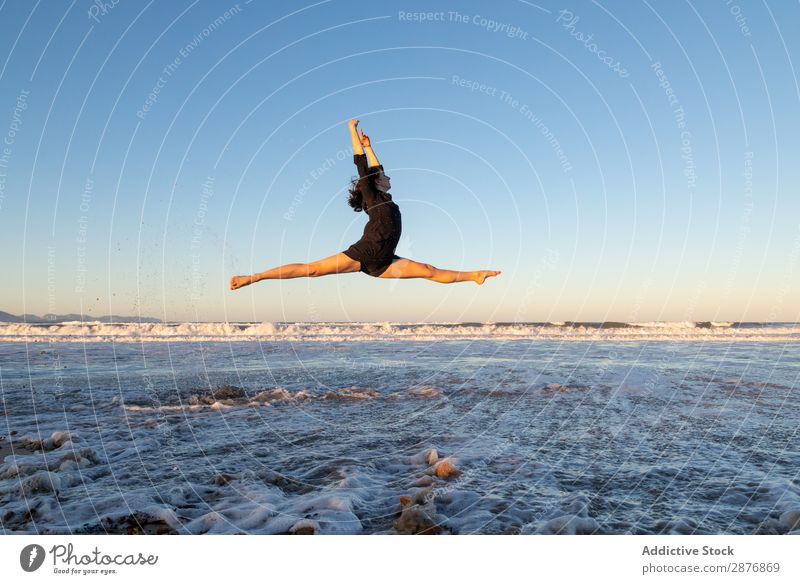 Woman jumping near water on shore Dancer Coast Water Jump Ocean Legs Side Air Sky waving Sand Blue Youth (Young adults) Ballet Lifestyle Beach
