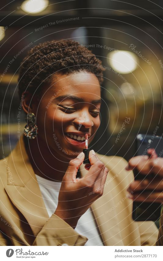 Stylish black woman rouging lips and holding smartphone on street Woman PDA Lips Street Black African-American Elegant Style Lipstick Closed eyes City Cellphone