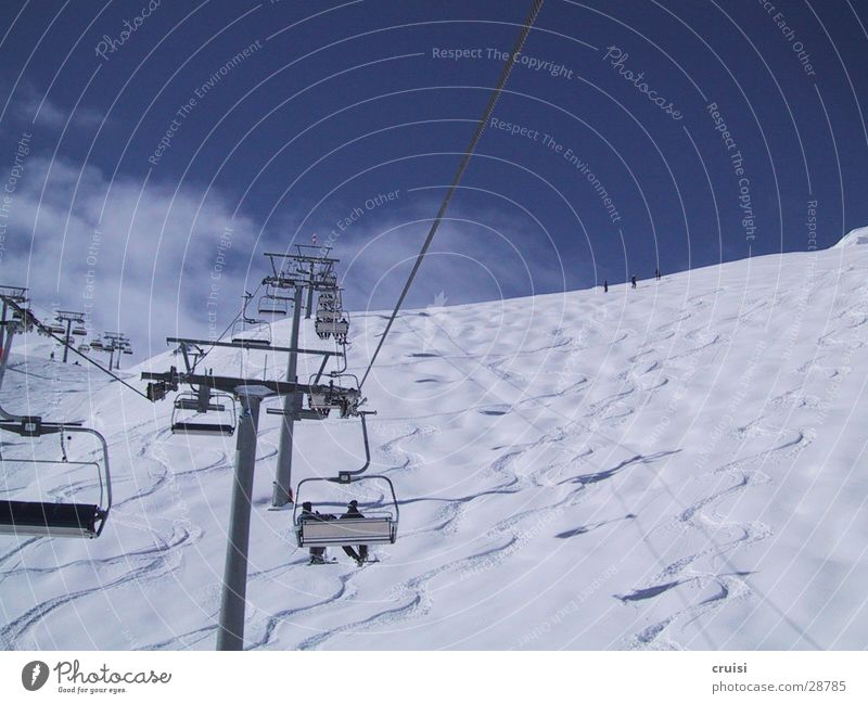 Sky Sun Clouds Snow Sports Skiing Tracks Upward Ski resort Austria Winter vacation Ski lift Chair lift Snowboarding Deep snow Ischgl