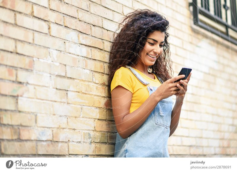 Young North African woman texting with her smart phone outdoors Lifestyle Style Happy Beautiful Hair and hairstyles Telephone PDA Technology Human being