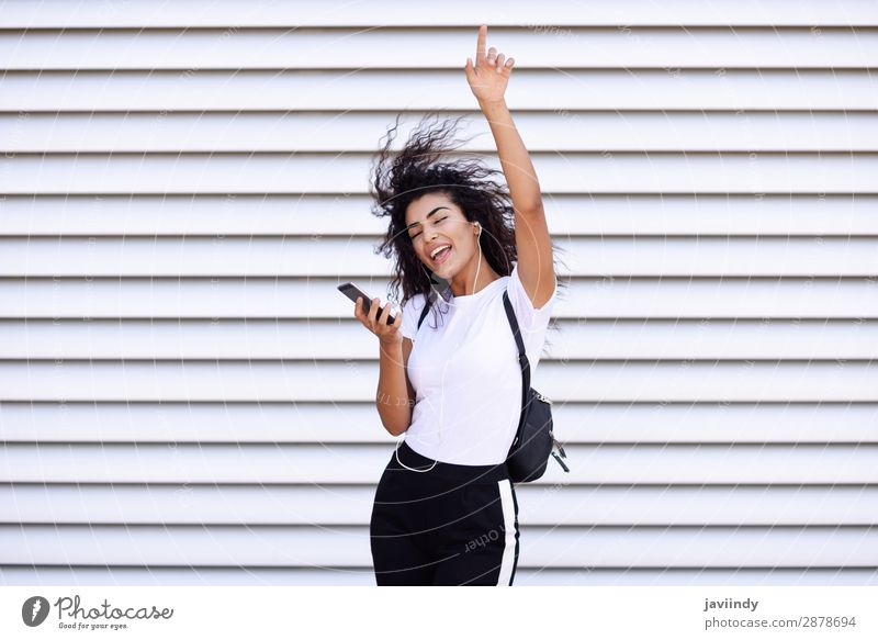 African woman listening to music with earphones and smartphone Woman Human being Youth (Young adults) Young woman Beautiful Joy 18 - 30 years Street Adults