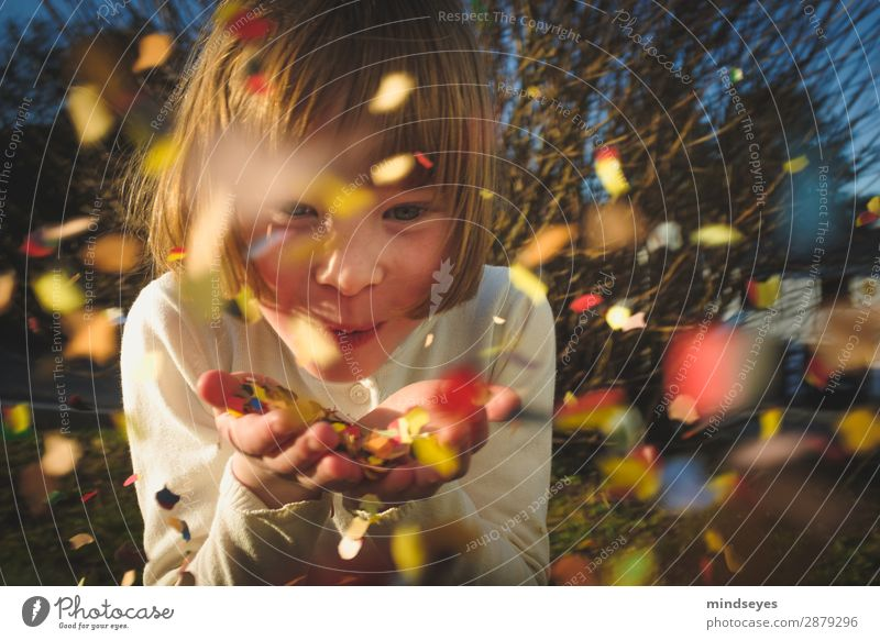Little girl blows confetti into the camera Carnival Infancy 1 Human being 3 - 8 years Child bushes Garden Blonde Confetti Feasts & Celebrations smile Playing