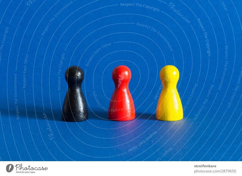 Three game pieces in black, red and yellow stand in a row on a blue background Economy Toys Wood Select Stand Blue Yellow Gold Red Black Acceptance Protection