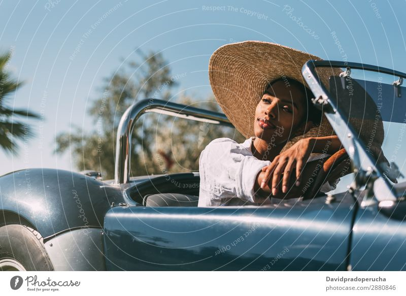 Black woman driving a vintage convertible car Woman Car Driving right steering wheel Ethnic Happy Convertible Street united kingdom Luxury Looking away