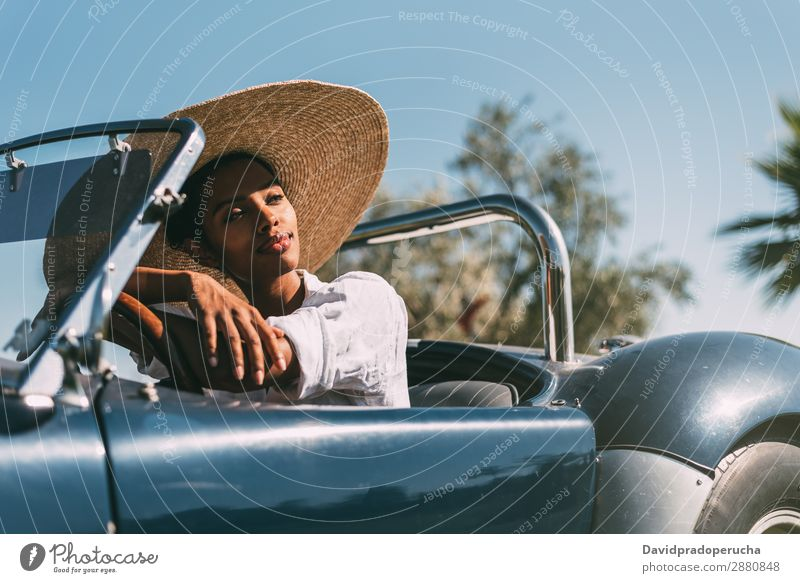 Black woman driving a vintage convertible car Woman Car Driving Ethnic Happy Convertible Street Luxury Looking away Smiling Classic 60's Beautiful cabriolet