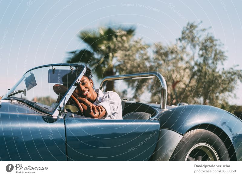 Black woman driving a vintage convertible car Woman Car Driving Happy Ethnic Convertible Street Luxury Looking into the camera Profile Cheerful Smiling Classic