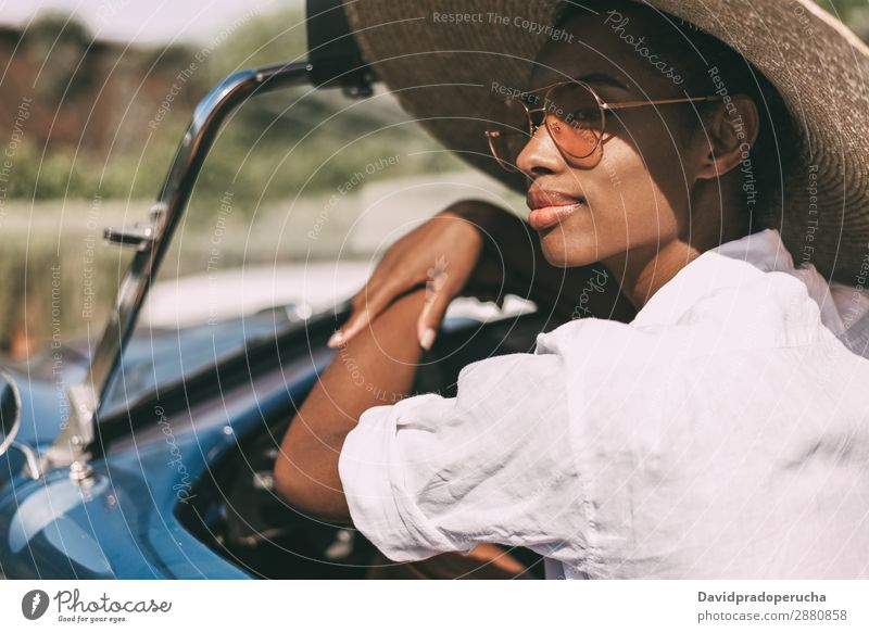 Black woman driving a vintage convertible car Woman Car Driving Ethnic Happy Convertible Street Luxury Looking away Smiling Classic 60's Beautiful Straw hat