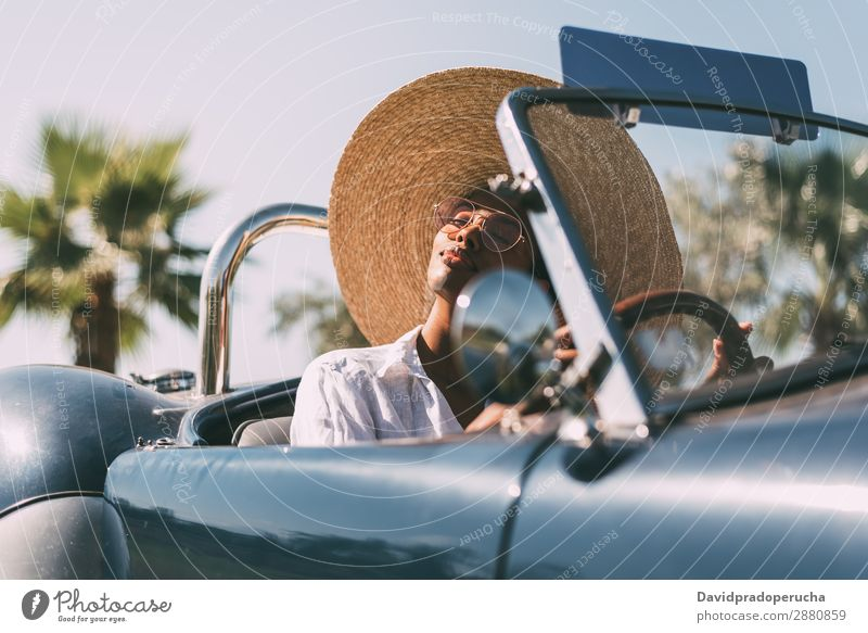 Black woman driving a vintage convertible car Woman Car Happy Driving right steering wheel Ethnic Convertible Street united kingdom Luxury Straw hat Sunglasses