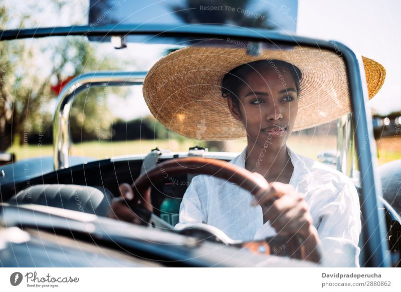 Black woman driving a vintage convertible car Woman Car Driving Ethnic Happy Convertible Street Luxury Looking away Front view Smiling Classic 60's Beautiful