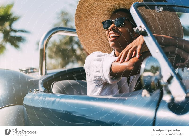 Black woman driving a vintage convertible car Woman Car Driving right steering wheel Ethnic Convertible Happy Street united kingdom Front view Vintage Luxury