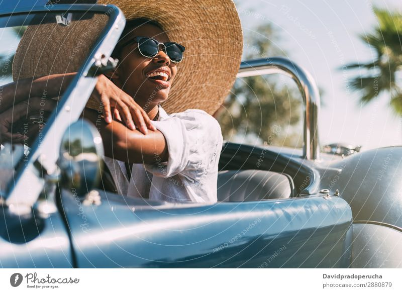 Black woman driving a vintage convertible car Woman Car Driving Ethnic Convertible Street Happy Classic Luxury Vintage Looking away Transport Cheerful Smiling