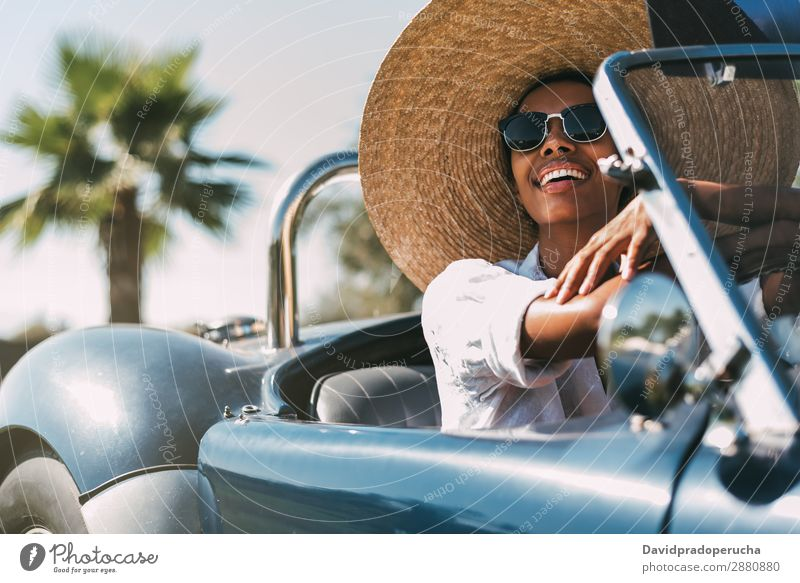 Black woman driving a vintage convertible car Woman Car Driving right steering wheel Ethnic Convertible Street united kingdom Vintage Front view Luxury