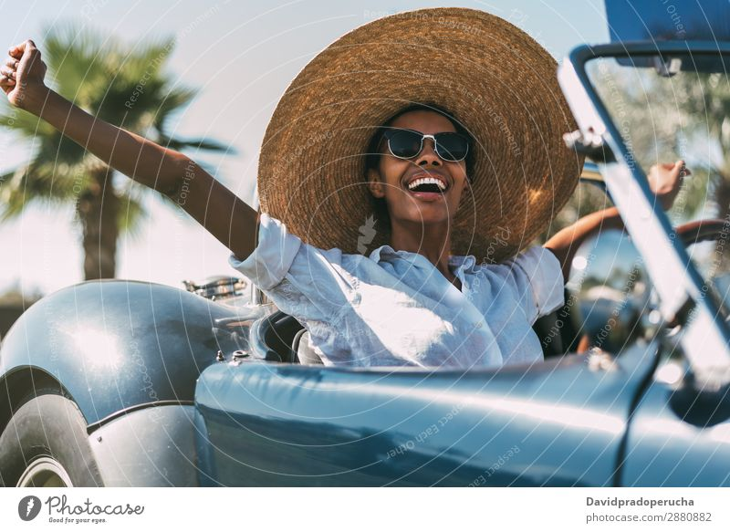 Black woman driving a vintage convertible car Woman Car Driving right steering wheel Ethnic Convertible Street united kingdom Front view Vintage Luxury