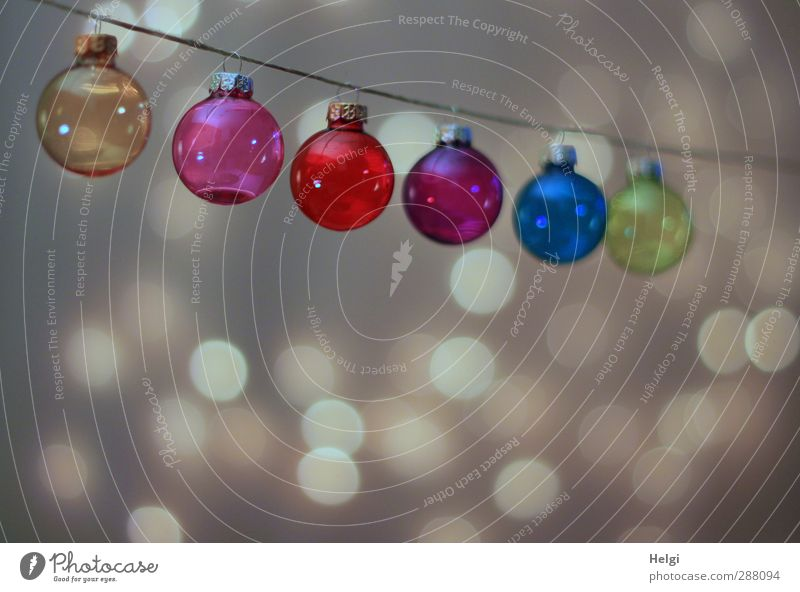 colourful glass Christmas tree balls hang on a string, with light points in the background Feasts & Celebrations Christmas & Advent Decoration Glitter Ball