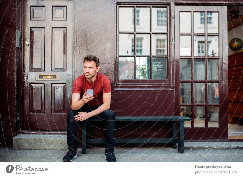 Man sitting in a bench on a beautiful maroon background Cellphone Caucasian Building Youth (Young adults) Architecture Technology