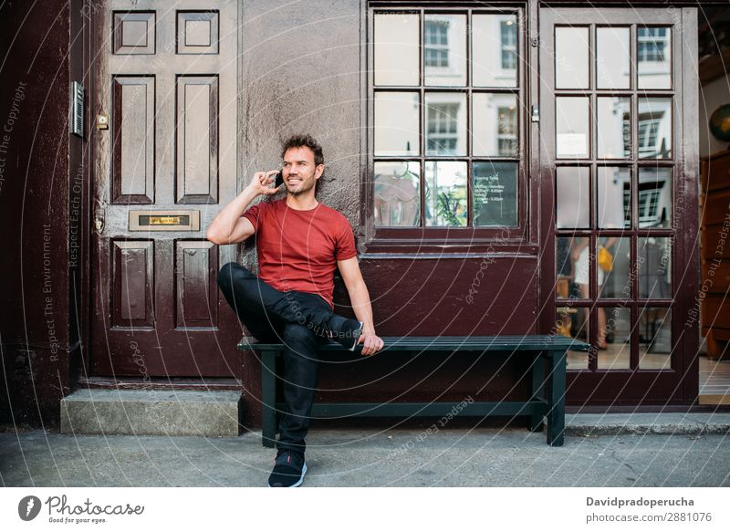 Man sitting in a bench on a beautiful maroon background Cellphone Caucasian Cheerful Building Youth (Young adults) Architecture