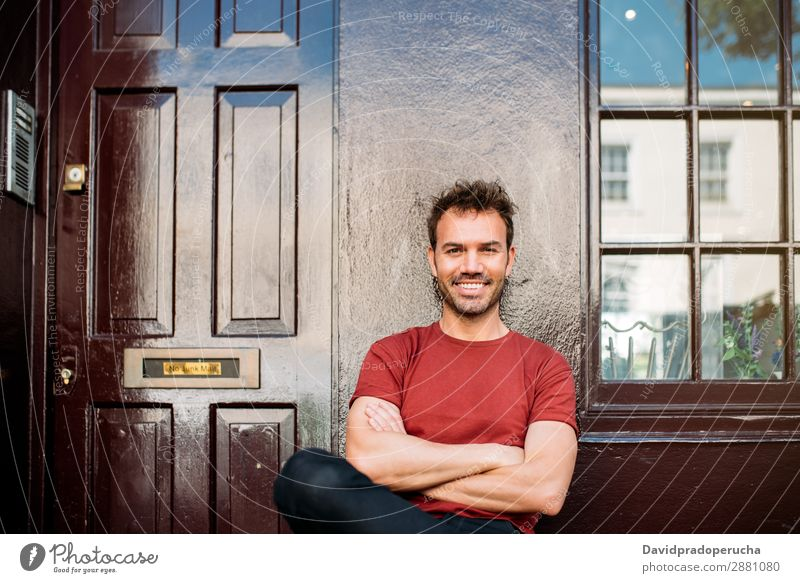 Man sitting in a bench on a beautiful maroon background Cheerful Caucasian Building Youth (Young adults) Happy Architecture Vintage Smiling Notting Hill decor