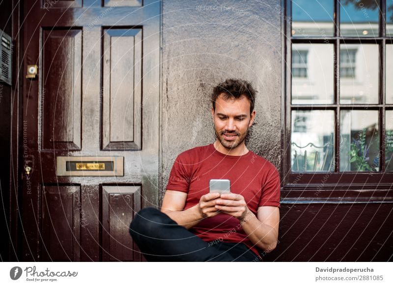 Man sitting in a bench on a beautiful maroon background Cellphone Caucasian Cheerful Building Youth (Young adults) Architecture Technology Vintage Smiling