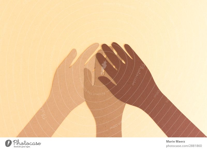Together against racism // Three hands in different skin colours made of paper hold together Team Human being by hand Positive Brown Acceptance Trust Solidarity