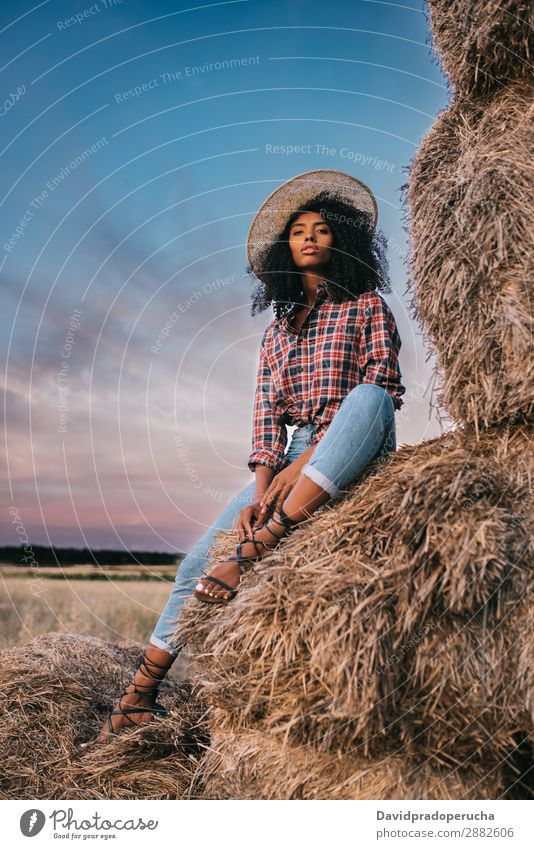 Happy black young woman sitting on a pile of hay Woman Farmer Hay Summer Ethnic Black African Landscape Nature Countries Sky Relaxation Lifestyle