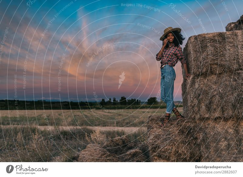 Happy black young woman standing on a pile of hay Woman Farmer Hay Summer Ethnic Black African Landscape Nature Countries Sky Relaxation Lifestyle