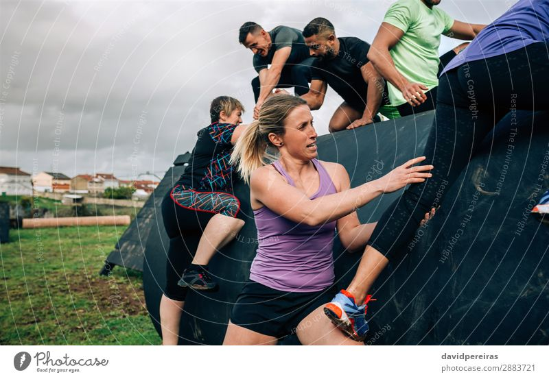 Participants in an obstacle course climbing a drum Lifestyle Sports Climbing Mountaineering Human being Woman Adults Man Group Authentic Strong Black Effort