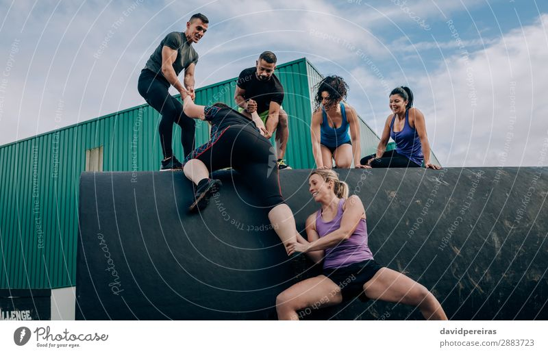 Participants in an obstacle course climbing a drum Lifestyle Joy Happy Sports Climbing Mountaineering Human being Woman Adults Man Group Smiling Authentic
