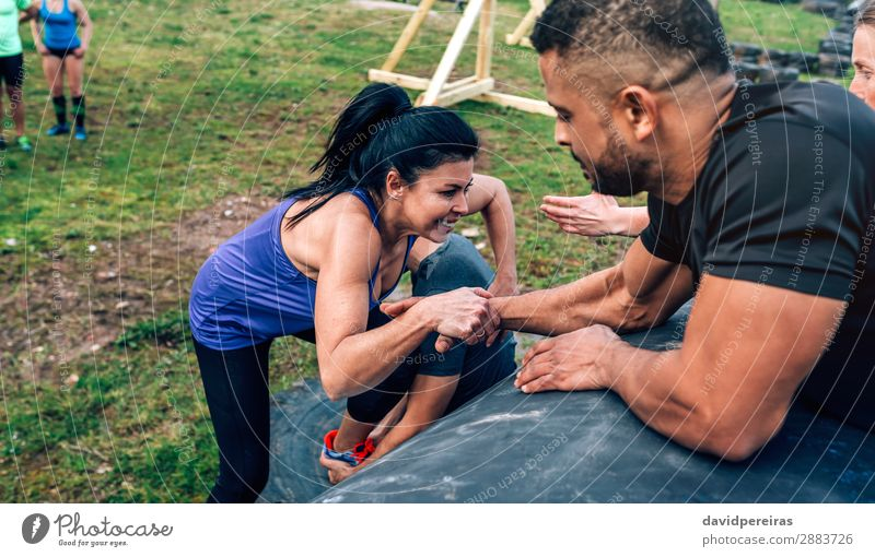 Woman in an obstacle course climbing a drum Lifestyle Joy Happy Sports Climbing Mountaineering Human being Adults Man Hand Group Authentic Strong Black
