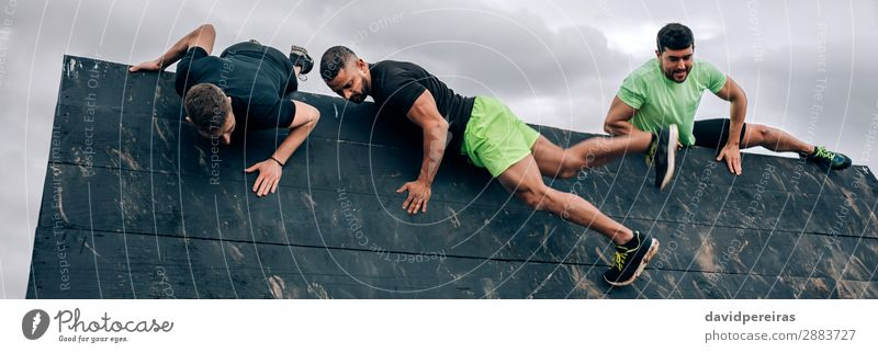 Participants in obstacle course climbing wall Sports Climbing Mountaineering Internet Human being Man Adults Group Strong Black Effort Energy Competition