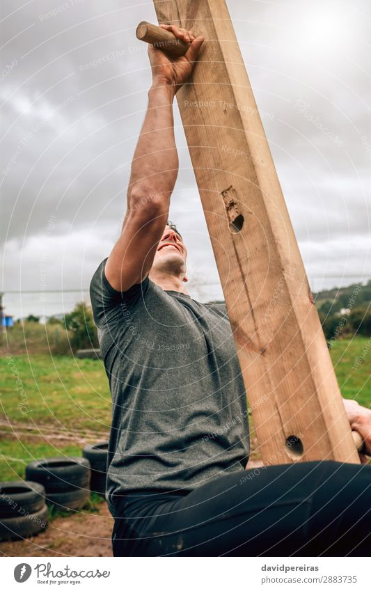Participant in a obstacle course doing pegboard Lifestyle Sports Climbing Mountaineering Human being Man Adults Wood Authentic Strong Power Effort Competition