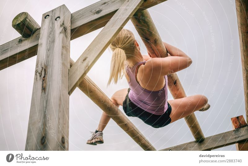 Participant in a obstacle course doing weaver Lifestyle Sports Human being Woman Adults Blonde Wood Authentic Above Strong Power Effort Competition