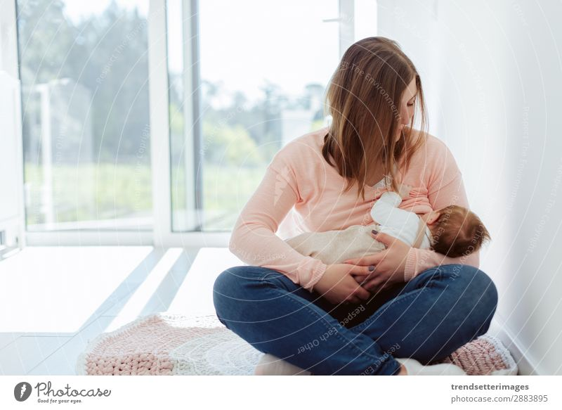 Young Mother breastfeeding newborn baby Eating Happy Beautiful Child Baby Woman Adults Parents Family & Relations Infancy Arm Feeding Love Small White
