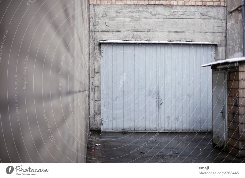 on the left Outskirts Industrial plant Factory Building Wall (barrier) Wall (building) Facade Garage door Cold Town Blue Gray Interior courtyard Colour photo