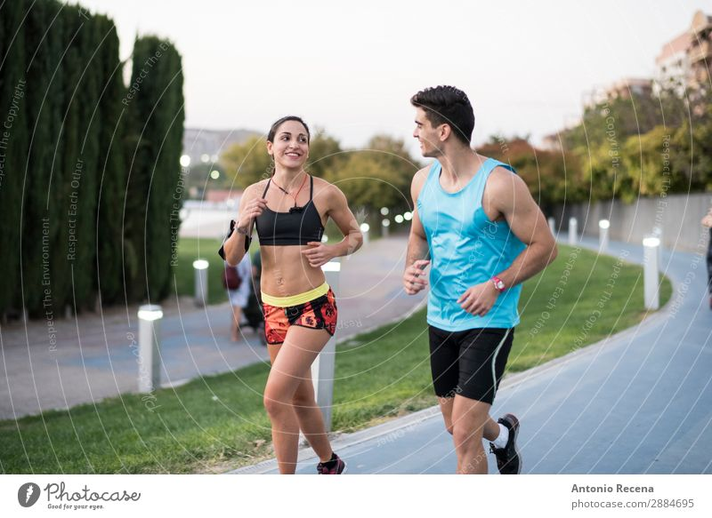 Couple running in city park Flirt Sports Human being Woman Adults Man 18 - 30 years Youth (Young adults) Brunette Fitness Running Together Beautiful Strong jog