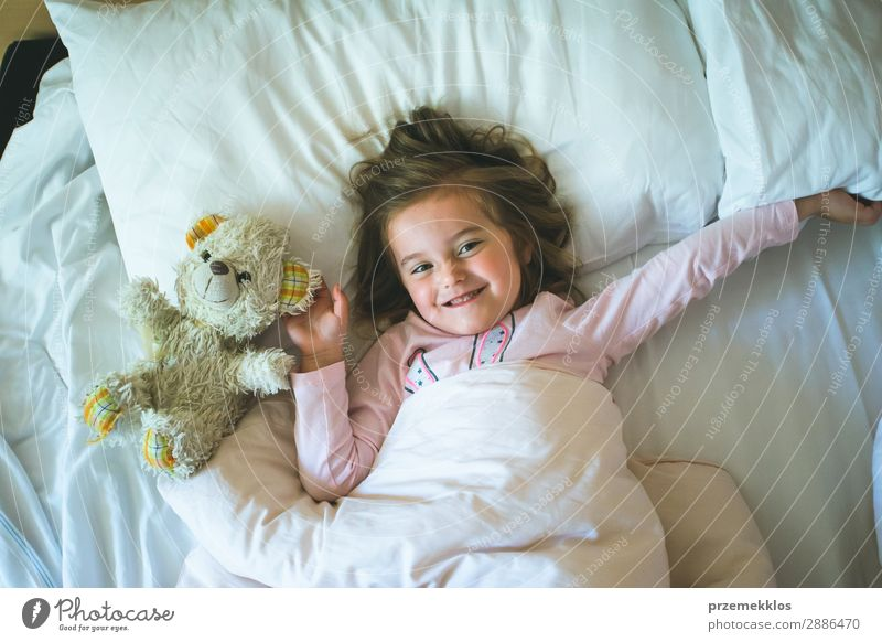 Little girl lying in a bed with teddy bear at the morning. Happy mornings. Bedtime. Weekend mornings Beautiful Playing Child Human being Woman Adults Toys